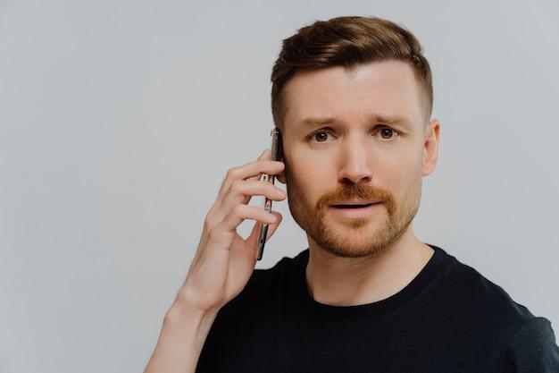 Close-up portret van een verbaasde jonge man die op een mobiele telefoon praat en zich ontevreden voelt na het ontvangen van slecht nieuws, kijkend naar de camera met bezorgde gezichtsuitdrukking, staande tegen de grijze studiomuur