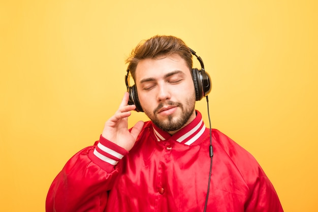 Close-up portret van een volwassen man luistert naar muziek in koptelefoon met gesloten ogen op geel