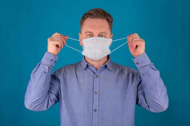 Close-up portret van een volwassen man met een medisch gezichtsmasker op blauwe achtergrond