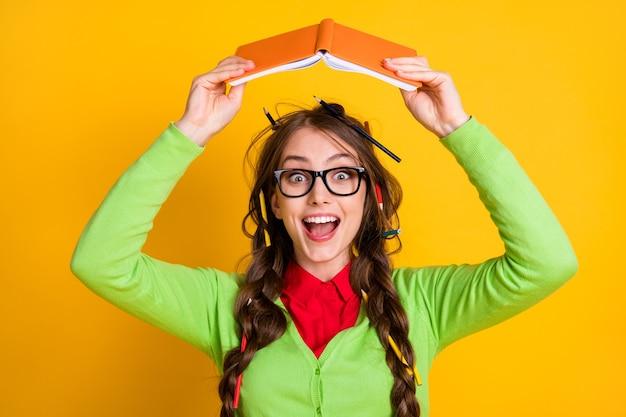 Close-up portret van een vrij funky, vrolijk tienermeisje met een werkboek boven het hoofd, alsof je plezier hebt geïsoleerd over een felgele achtergrond