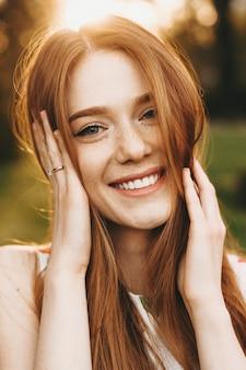 Close-up portret van een vrolijke jonge vrouw met lang rood haar en sproeten die direct glimlachend kijken terwijl ze beide handen op haar haar houdt tegen zonsondergang.