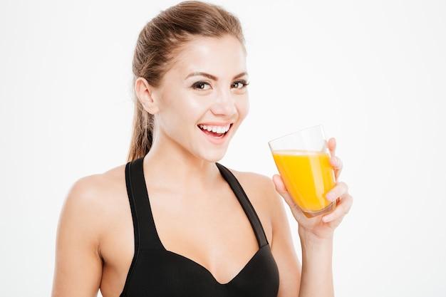 Close-up portret van een vrolijke lachende vrouw met een glas sinaasappelsap geïsoleerd