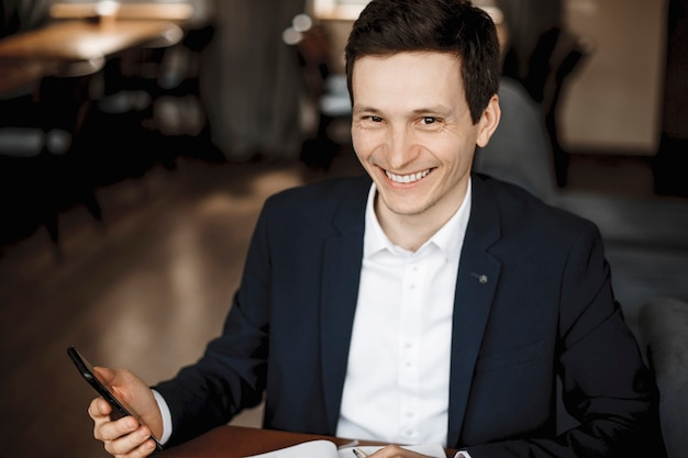 Close-up portret van een vrolijke zakenman kijken naar de camera glimlachen terwijl hij een smartphone vasthoudt.