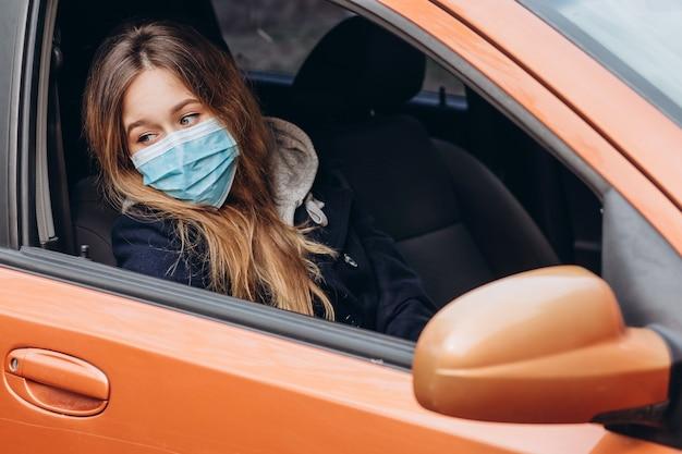 Close-up portret van een vrouw in een medisch masker in een auto. corona-epidemie. sars-cov-2. stop covid-19.