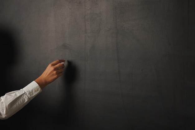 Close-up portret van een vrouwelijke hand met krijt op een leeg zwart glanzend schoolbord