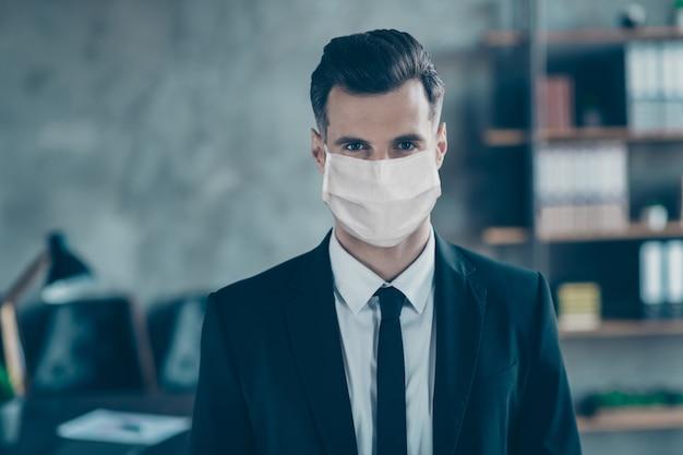 Close-up portret van een zakenman die een katoenen veiligheidsmasker draagt, ademhalingsziekte op de werkplek