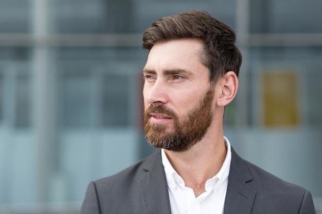 Close-up portret van een zakenman met een mooie baard, een man in een pak die terugkijkt