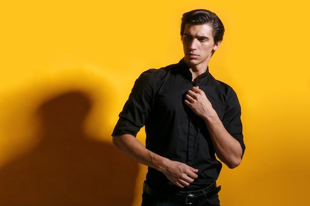 Close-up portret van een zelfverzekerde jonge man met kapsel in zwarte kleding, poseren in profiel op gele achtergrond.