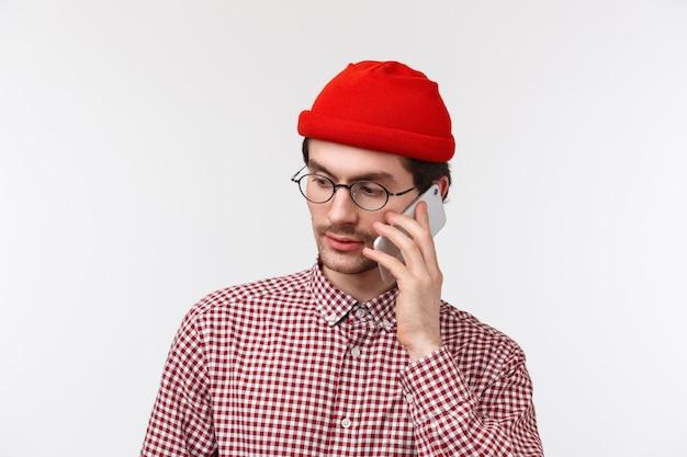 Close-up portret van ernstig uitziende jonge man in rode muts en bril iemand bellen op mobiele telefoon, een gesprek voeren, zijwaarts kijken als een bestelling plaatsen of een reservering bevestigen,