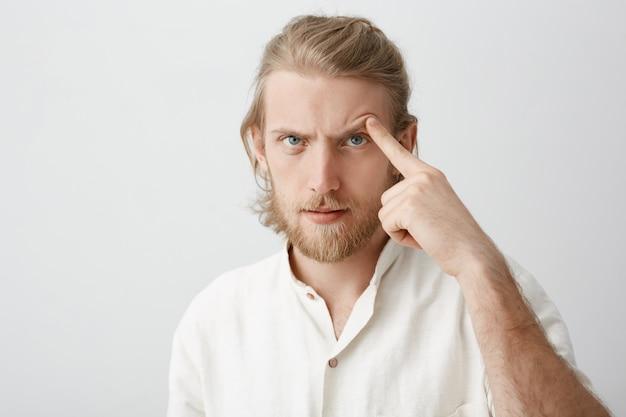 Close-up portret van ernstige aantrekkelijke bebaarde man met blond haar, wenkbrauw met wijsvinger optillen alsof hij iemand probeert te bedreigen of bang te maken