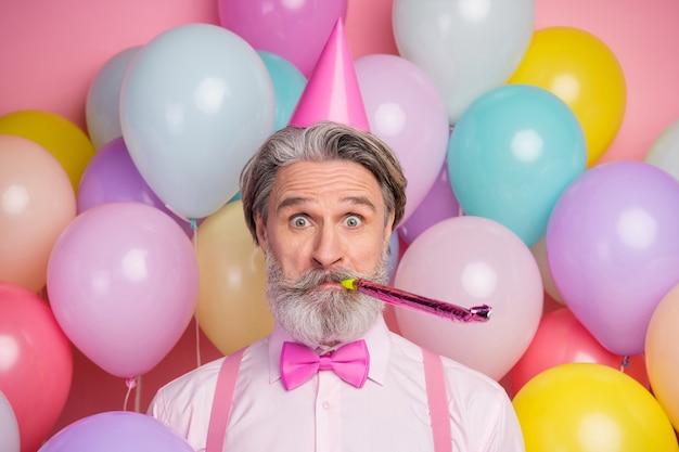 Close-up portret van funky man waait feestelijk fluitje op ballon achtergrond