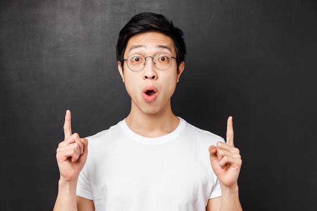 Close-up portret van geamuseerd en opgewonden gelukkig aziatisch man bezoekt pretpark voor het eerst, wijzende vingers naar iets super cools, zeg wow verbaasd, sta op een zwarte muur