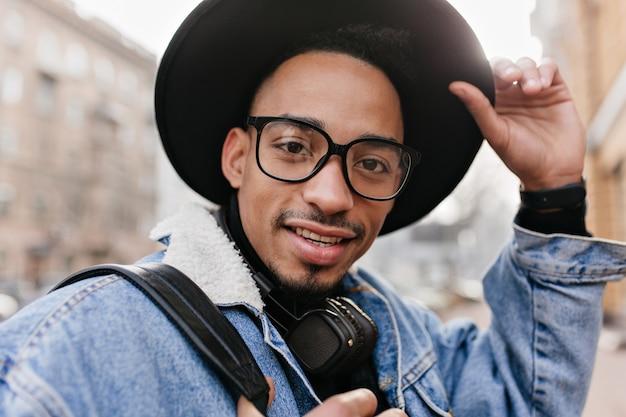 Close-up portret van geïnteresseerde afrikaanse man draagt elegante hoed. buiten foto van knappe zwarte man in spijkerjasje.