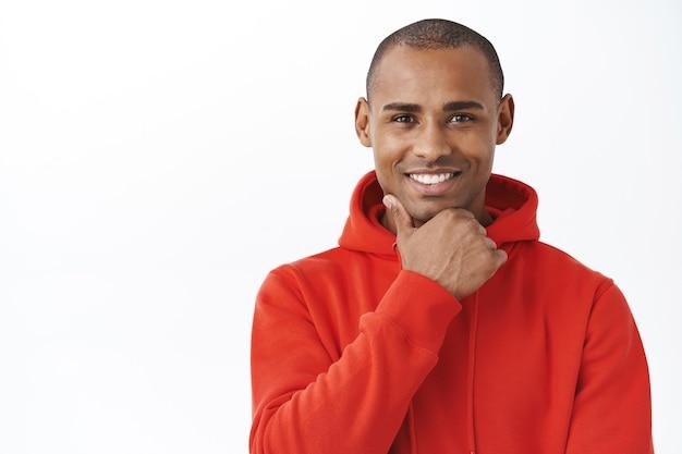 Close-up portret van geïntrigeerde, afro-amerikaanse knappe man die een beslissing neemt, een interessant aanbod ziet, overweeg om het aan te nemen