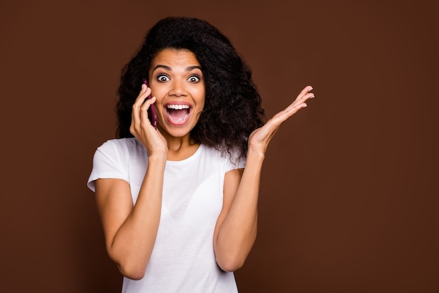Close-up portret van gekke grappige afro amerikaanse jeugd meisje praten slimme telefoon met vriend onder de indruk grote koopje informatie schreeuw wow omg draag wit t-shirt.