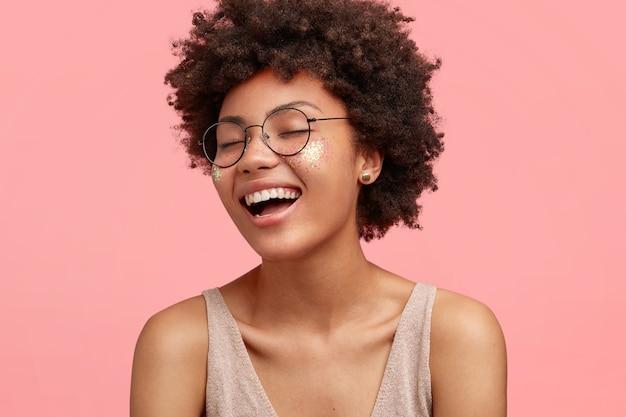 Close-up portret van gelukkig afro-amerikaanse vrouw lacht om iets grappigs, positieve uitdrukking heeft, draagt een bril, heeft krullend haar, nonchalant gekleed, sluit de ogen met geluk, geïsoleerd op roze