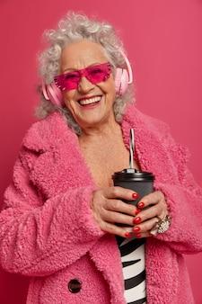 Close-up portret van gelukkig gerimpelde modieuze oma roze panty en jas dragen
