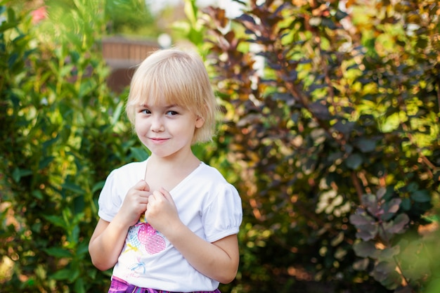 Close-up portret van gelukkig klein blobde meisje in de lagere school leeftijd buitenshuis in groen park