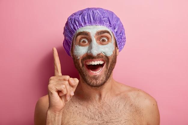 Close-up portret van gelukkig mannelijk model verhoogt wijsvinger, naar boven wijst, draagt kleimasker op gezicht