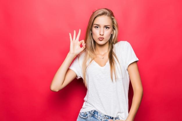 Close-up portret van gelukkig meisje gebaren ok teken geïsoleerd op rode achtergrond