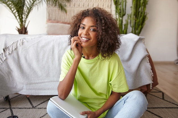 Close-up portret van gelukkig mooie donkere huid vrouw met charmante glimlach kijken, poseren over interieur, spijkerbroek en geel t-shirt dragen Gratis Foto