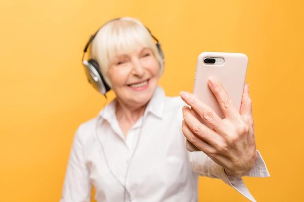 Close-up portret van gelukkig vrolijk opgewonden heerlijk met brede glimlach oma grootmoeder oma met een video-oproep via internet, geïsoleerd op gele achtergrond.