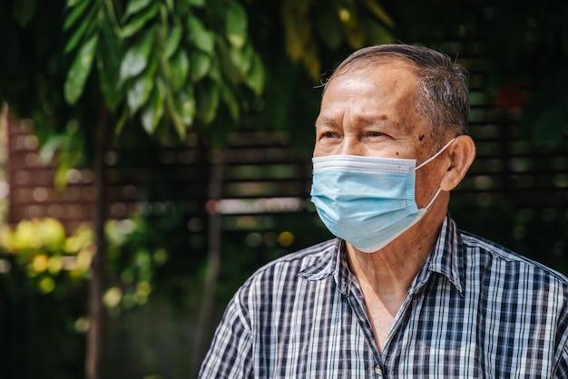 Close-up portret van gelukkige aziatische senior man draagt een masker kijk met hoop. oude thaise man
