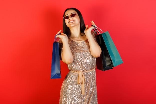 Close-up portret van gelukkige jonge brunette vrouw in rode zonnebril en jurk met kleurrijke boodschappentassen op zoek weg geïsoleerd op rode achtergrond
