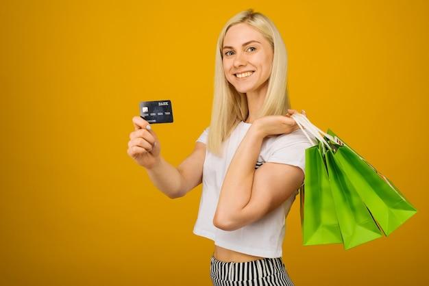 Close-up portret van gelukkige jonge mooie blonde vrouw met creditcard en groene boodschappentassen, camera kijken, op geel