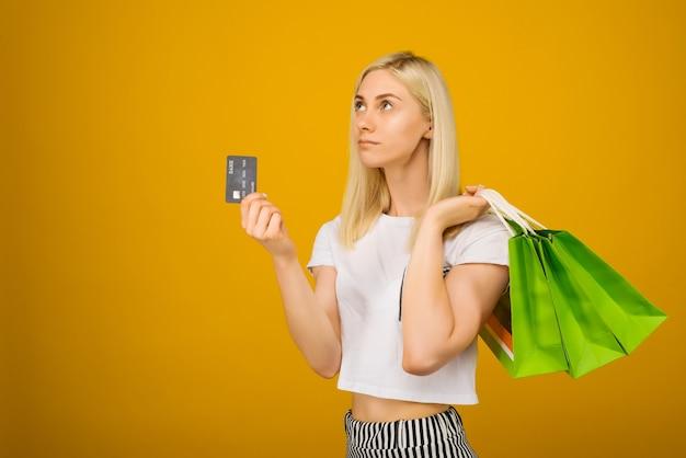 Close-up portret van gelukkige jonge mooie blonde vrouw met creditcard en groene boodschappentassen, op geel