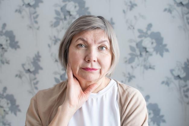 Close-up portret van gelukkige senior vrouw met grijs haar glimlachen is op zoek naar de camera