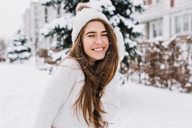 Close-up portret van gelukkige vrouw in wollen trui genieten van winter momenten. buiten foto van langharige lachende dame in gebreide muts met plezier in besneeuwde ochtend