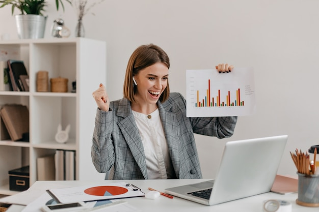 Close-up portret van gelukkige zakenvrouw in stijlvolle outfit. meisje in opgewekte stemming toont grafiek via skype.
