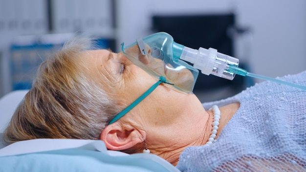 Close-up portret van gepensioneerde vrouw die ademt met moeilijkheden in zuurstofmasker liggend in ziekenhuisbed tijdens covid-19 coronavirus uitbraak. medische geneeskunde gezondheidszorg. infectie behandeling