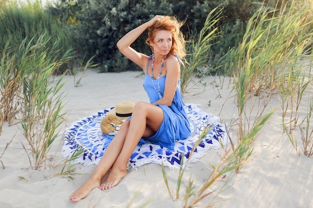 Close-up portret van geweldige lachende roodharige vrouw in blauwe jurk ontspannen op lente zonnig strand op handdoek. strohoed, stijlvolle armbanden en ketting.