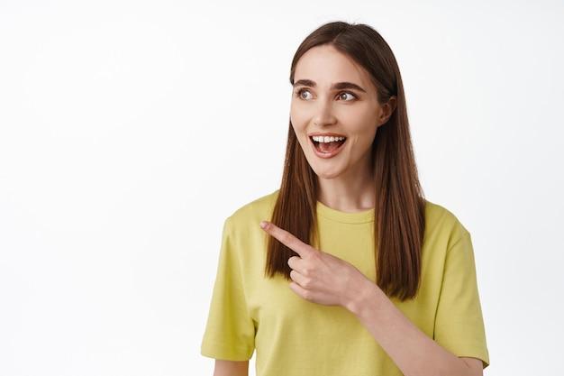 Close-up portret van glimlachend verbaasd 20s meisje, hijgend gefascineerd door iets cools op wit.