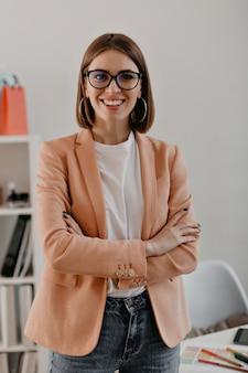 Close-up portret van glimlachende kortharige zakenvrouw in wit t-shirt poseren met armen gekruist in wit kantoor.