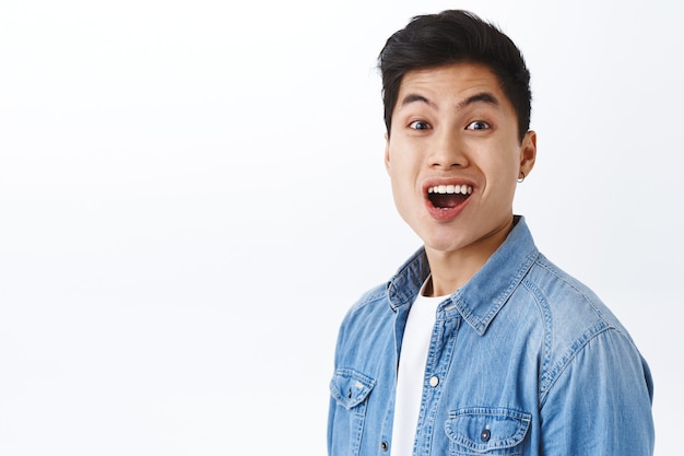 Close-up portret van grappige opgewonden, gelukkige aziatische man die zich verheugt over goed nieuws, glimlachend stralende gezichtsuitdrukking, onder de indruk en vrolijk, plezier hebbend op een witte muur