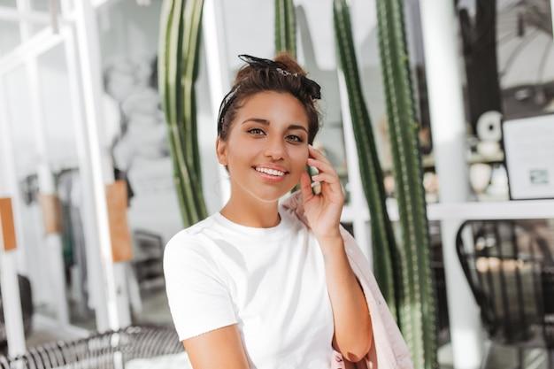Close-up portret van groenogige brunette vrouw in haarband en wit t-shirt tegen muur van ramen en cactussen