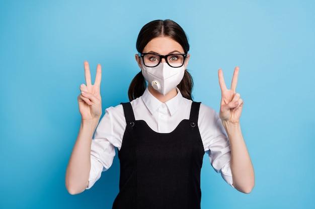 Close-up portret van haar, mooi, aantrekkelijk, funky, gezond meisje met een veiligheids n95-ademhalingsmasker met dubbel v-teken stop mers cov griepziekte optimistisch geïsoleerde blauwe kleur achtergrond
