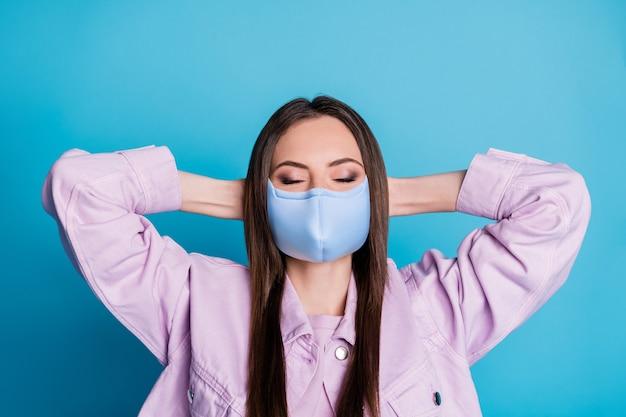 Close-up portret van haar, mooi, aantrekkelijk, gezond meisje met textiel herbruikbaar veiligheidsmasker rustende virale besmettelijke longontsteking preventie geïsoleerd helder levendig glans levendige blauwe kleur achtergrond