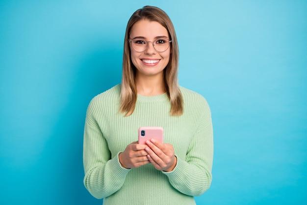 Close-up portret van haar mooi uitziende aantrekkelijke mooie mooie vrolijke vrolijke meisje met behulp van digitaal apparaat vrije tijd geïsoleerd over heldere levendige glans levendige blauwe kleur achtergrond