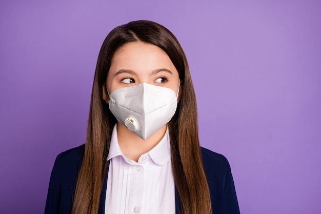 Close-up portret van haar mooie aantrekkelijke langharige schoolkind met n95 veiligheidsmasker gasmasker mers cov preventie co2 luchtvervuiling denken geïsoleerd op violet lila paarse kleur achtergrond
