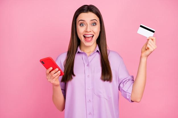 Close-up portret van haar mooie aantrekkelijke mooie mooie charmante blije vrolijke vrolijke langharige meisje met behulp van mobiele bankkaart kopen online bestelling geïsoleerd over roze pastel kleur achtergrond