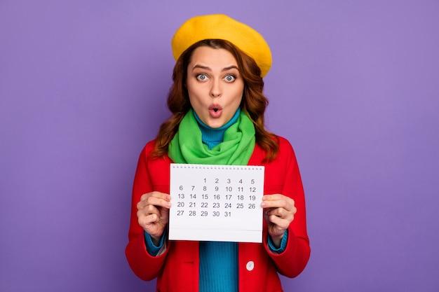 Close-up portret van haar mooie aantrekkelijke mooie mooie charmante verbaasd verbijsterd golvend-haired meisje in handen houden papier kalender dag tijd geïsoleerd op violet lila paarse pastel kleur achtergrond Premium Foto