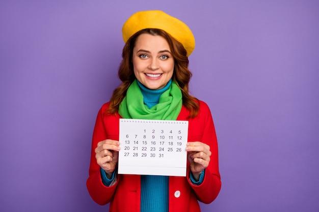 Close-up portret van haar mooie aantrekkelijke mooie mooie charmante vrolijke vrolijke golvende haren meisje in handen houden papieren kalender geïsoleerd op violet lila paarse pastel kleur achtergrond
