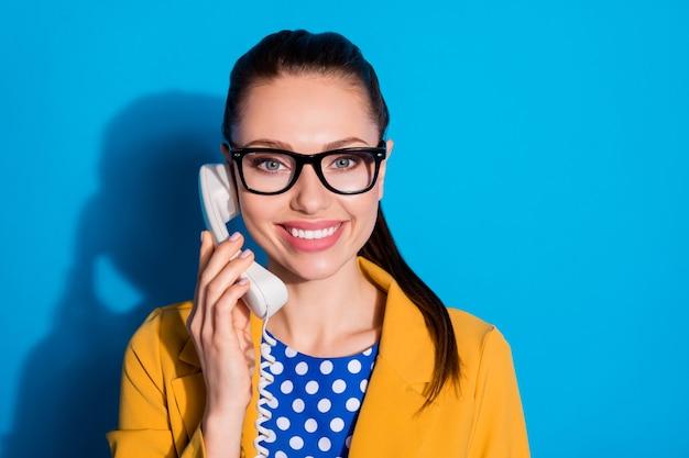 Close-up portret van haar mooie, charmante, mooie, vrolijke meid-operator die de inkomende oproepdienst 24/7 afhandelt, geïsoleerd op een heldere, levendige glans, een levendige blauwe kleurachtergrond