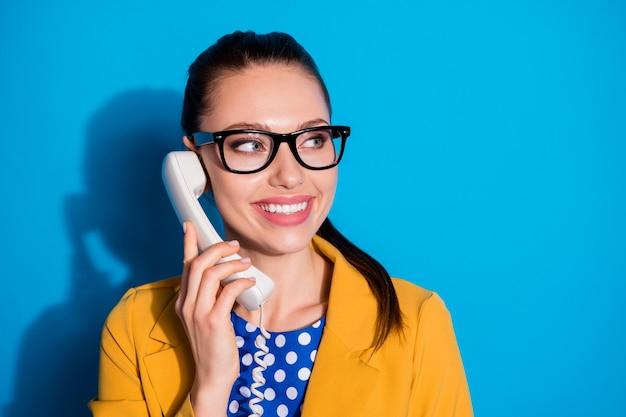 Close-up portret van haar mooie, charmante, vrolijke, vrolijke meid-operator die 24/7 inkomende oproepservice op afstand biedt, geïsoleerd op heldere, levendige glans, levendige blauwe kleurachtergrond