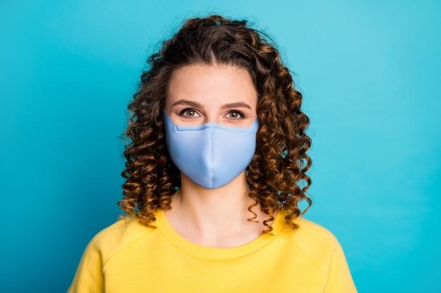 Close-up portret van haar mooie, gezonde vriendin met golvend haar die herbruikbare veiligheidstextielmasker draagt ademhalingsapparaat stop grippe griep geïsoleerd helder levendig glans levendige blauwe kleur achtergrond