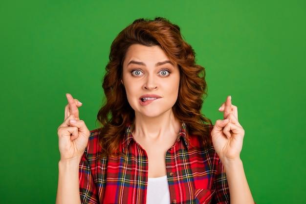 Close-up portret van haar mooie, mooie, bezorgde, golvende meisjesventilator met een geruit overhemd gekruiste vingers verwacht geïsoleerd over heldere levendige glans levendige groene kleur achtergrond